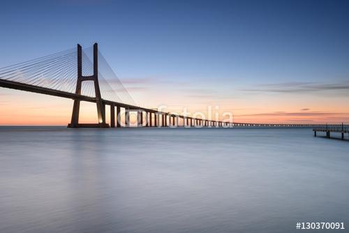 Ponte Vasco da Gama przy wschodem słońca Rio Tejo, Lisbon, Portugalia.
