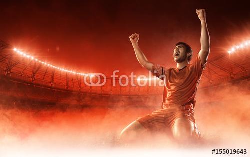 piłkarz na stadion piłkarski świętuje bramkę na czerwonym tle dymu