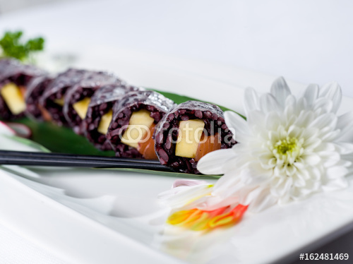 Czarna ryżowa suszi rolka z białym kwiatem