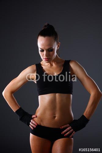 Mięśniowa młodej kobiety pozycja na szarym tle