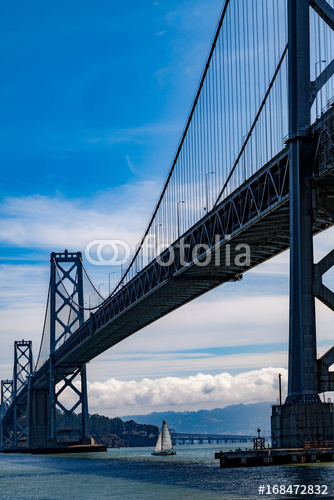 Oakland bay bridge with sailboat boat underneath