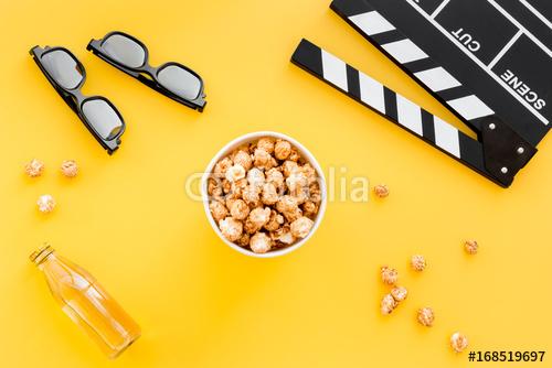 Przekąski do oglądania filmów. Popkorn i sodowany pobliski clapperboard, szkła na żółtym tło odgórnego widoku copyspace