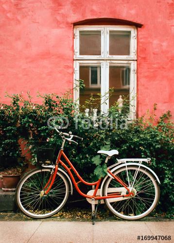 Rower stoi na ulicy w pobliżu starej różowej ściany